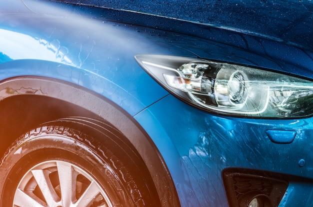 スポーツとモダンなデザインの青いコンパクトsuv車は水で洗っています。カーケアサービスビジネスコンセプト。高圧水スプレーで洗浄した後、水滴で覆われた車 Premium写真