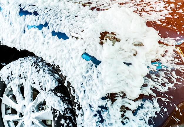 スポーツと石鹸で洗うモダンなデザインの青いコンパクトsuv車。車は白い泡で覆われています。カーケアサービスビジネスコンセプト。 Premium写真