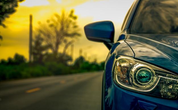 日没時にアスファルト道路に駐車された豪華な青色suv車の正面図 Premium写真