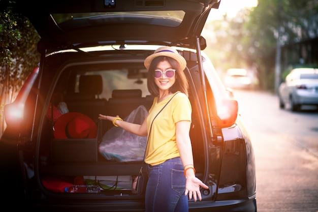 旅行者女性こぼれるような笑顔幸せ感感情休暇の時間に道路旅行の準備ができてsuv車の後ろに立っています。 Premium写真