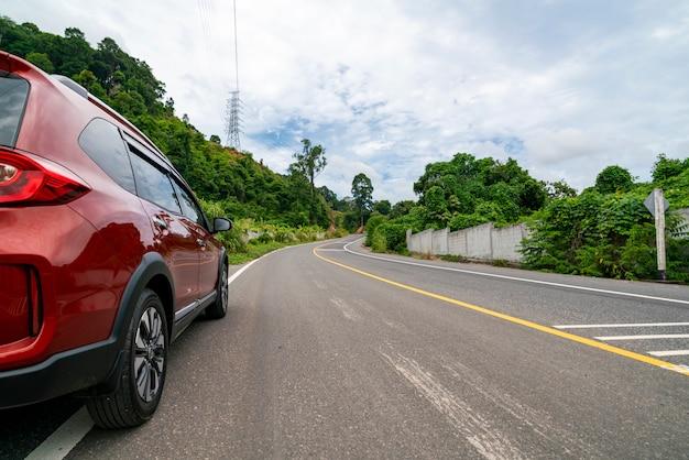 山緑の森とアスファルトの道路に赤いsuv車 Premium写真