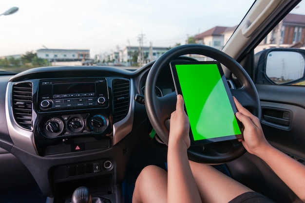 Suv車で空白の緑色の画面モニターとタブレットを使用して女性の手 Premium写真