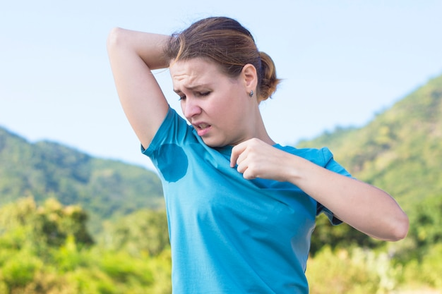 Sweating young girl sniffing her armpit, looking at the spot, sweat stain on her t-shirt with disgust emotion, face, frowns. upset frustrated woman suffering from hyperhidrosis. summer sunny hot day Premium Photo