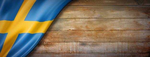 Sweden flag on vintage wood wall. horizontal panoramic banner. Premium Photo
