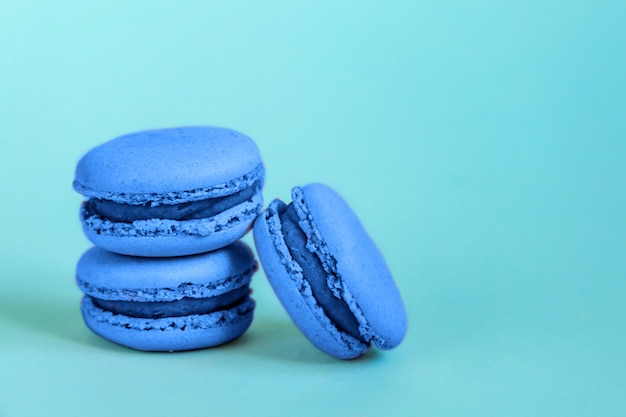 Sweet almond macaron or macaroon dessert cake colored in trendy color of year 2020 classic blue isolated on blue pastel background. macro using color . copyspace. Premium Photo
