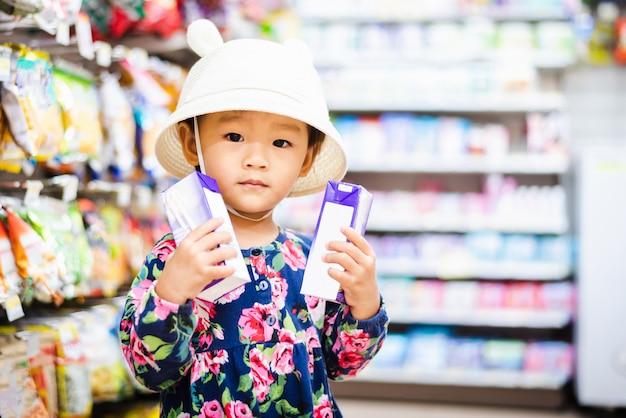 Sweet asian girl shopping in mini mart with basket, enjoy buying thing in mart Premium Photo