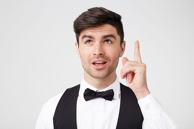 Sweet attractive handsome man with bowtie in a suit poins with index finger up as has a great idea Free Photo