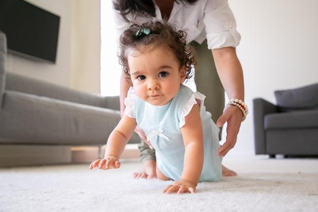 집에서 바닥에 크롤 링하는 달콤한 아기, 엄마의 손은 팔에 아이를 데려 갈 것입니다. 부모와 어린 시절 개념 무료 사진