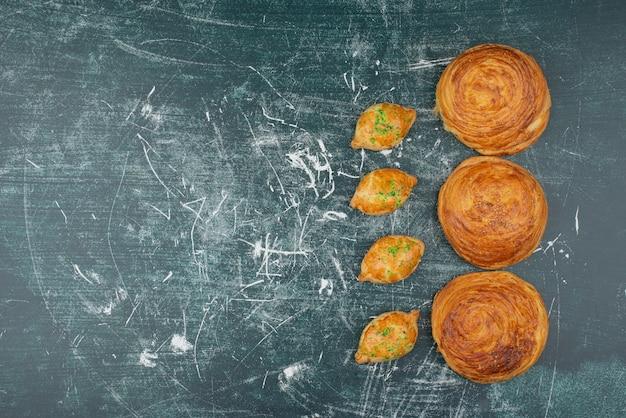 大理石のテーブルの上の甘いパン屋とgoglas。 無料写真