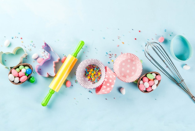 Sweet baking  for easter,  cooking  with baking - with a rolling pin, whisk for whipping, cookie cutters, sugar sprinkling, flour. light blue background, top view copyspace Premium Photo