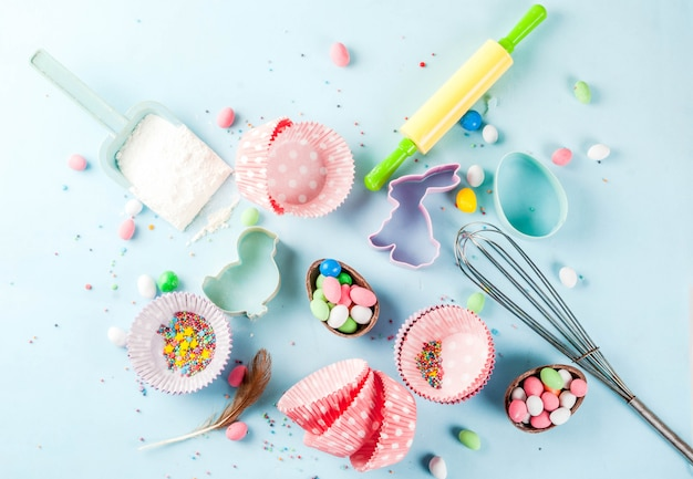 Sweet baking  for easter,  cooking  with baking  with a rolling pin, whisk for whipping, cookie cutters, sugar sprinkling, flour. light blue , top view copyspace Premium Photo