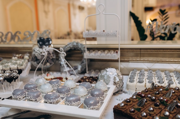 Sweet bar with grey mousse desserts, chocolate cake and candy pops Free Photo