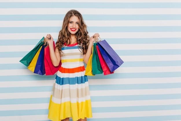 縞模様の壁にカラフルなショッピングバッグでポーズをとってカラフルなドレスの真っ赤な口紅と甘くて美しいブルネット 無料写真