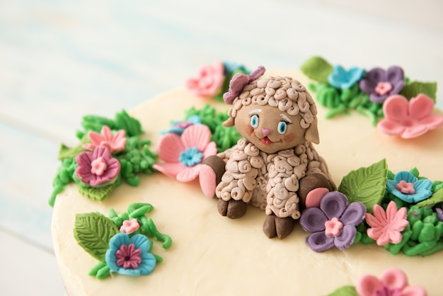 花と砂糖羊で飾られた甘い誕生日ケーキ Premium写真