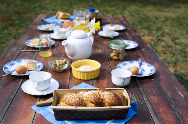Sweet bread and breakfast food on wooden table in the home yard. Premium Photo