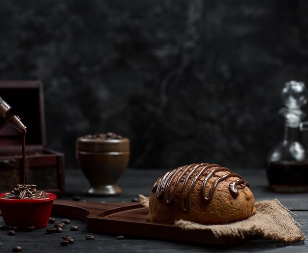 Sweet bread bun with chocolate syrup and chocolate icecream Free Photo