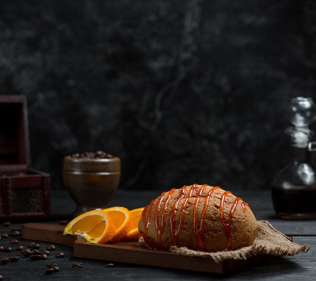 Sweet bun with cherry syrup and sliced orange fruit Free Photo