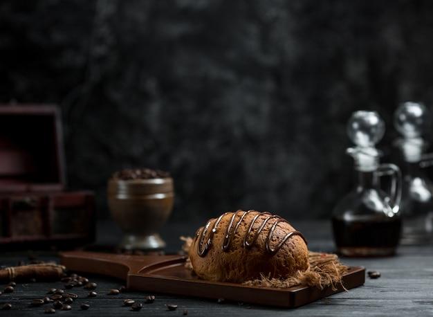 Sweet bun with chocolate syrup on it Free Photo