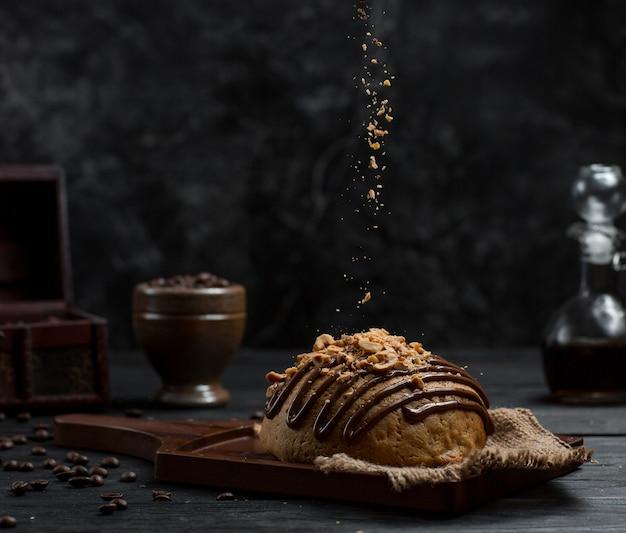 Sweet bun with chocolate syrup and peeled orange Free Photo