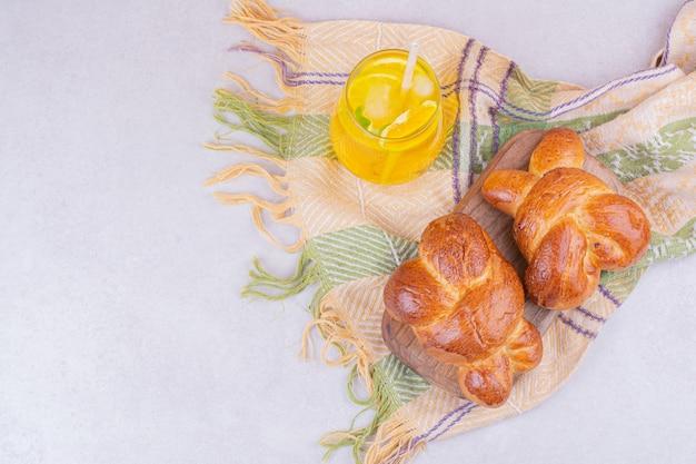 レモンジュースのグラスと甘いパン 無料写真