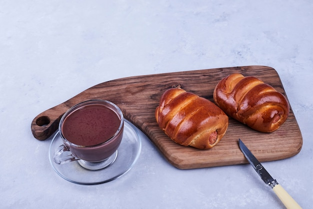 Sweet buns on a wooden board with a cup of hot chocolate on blue Free Photo