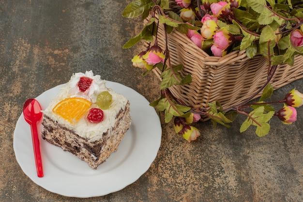 大理石の表面にバラのバスケットと甘いケーキ 無料写真