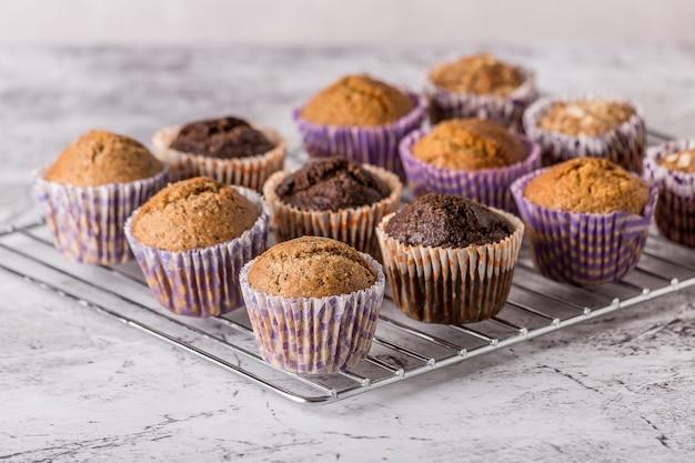 明るい大理石の背景に甘いケーキやカップケーキ。ホリデーケーキのお祝い、おいしいデザート、クローズアップ Premium写真