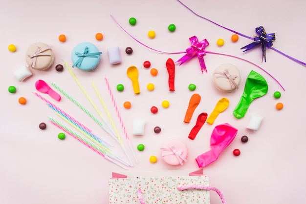 Sweet candies; macaroon; balloons; and ribbons over the shopping bag Free Photo