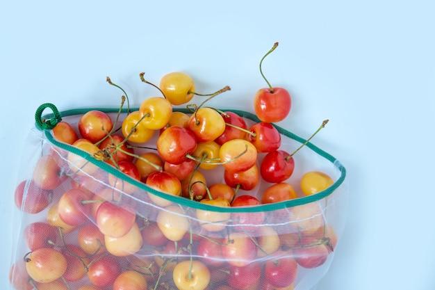 環境に優しいパッケージの甘いチェリー。野菜や果物の再利用可能なバッグ。店での買い物、小売。環境にやさしい包装。 Premium写真