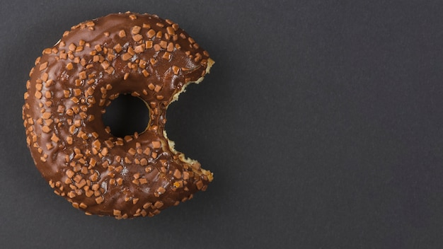 Sweet chocolate bitten donut on black background Free Photo