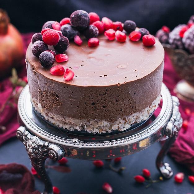 Torta al cioccolato dolce con semi di melograno e frutti di bosco freschi sopra Foto Gratuite