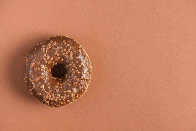 Sweet chocolate glazed donut decorated with sprinkles Free Photo