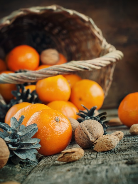 Sweet christmas composition with basket, tangerines, pine cones Premium Photo