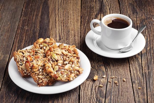 ナッツと古い木製のテーブルの上にコーヒーカップの甘いクッキー Premium写真