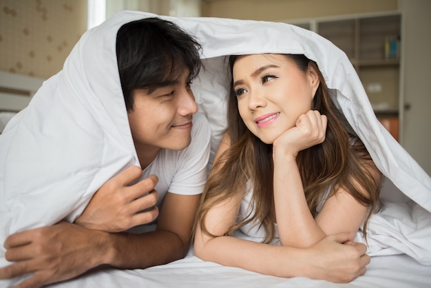 Sweet couple playing under the blanket on the bed Free Photo