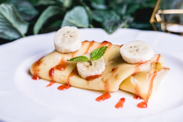 Sweet crepe filled with banana set on table. Premium Photo