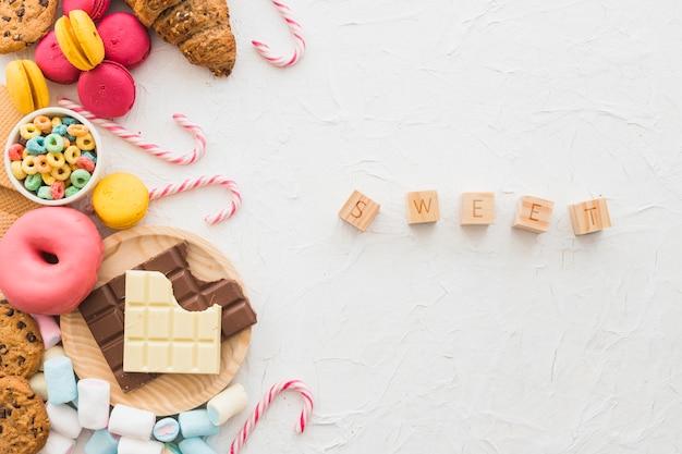 Sweet cubic blocks near unhealthy food on white backdrop Free Photo