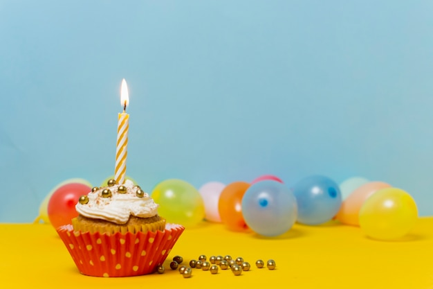 Sweet cupcake with lit candle on it and copy space Free Photo