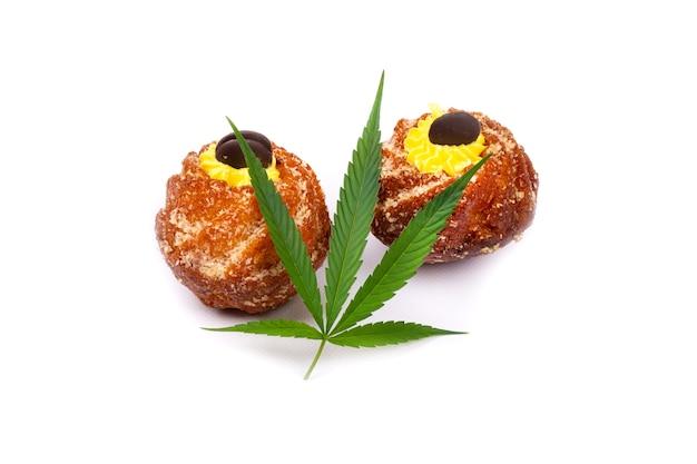白い背景で隔離のマリファナの葉と甘いカップケーキ。 Premium写真
