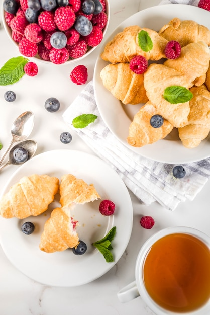 Sweet  dessert, homemade baked mini croissants with berry jam, served with tea, fresh raspberries, blueberries and mint Premium Photo