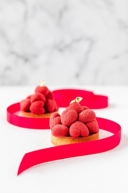 Sweet dessert tartelettes with red mousse hearts on top, decorated with a ribbon Premium Photo