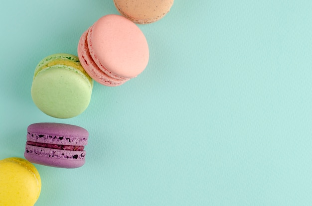 Sweet french desserts of different colors macaroons on pastel blue Premium Photo