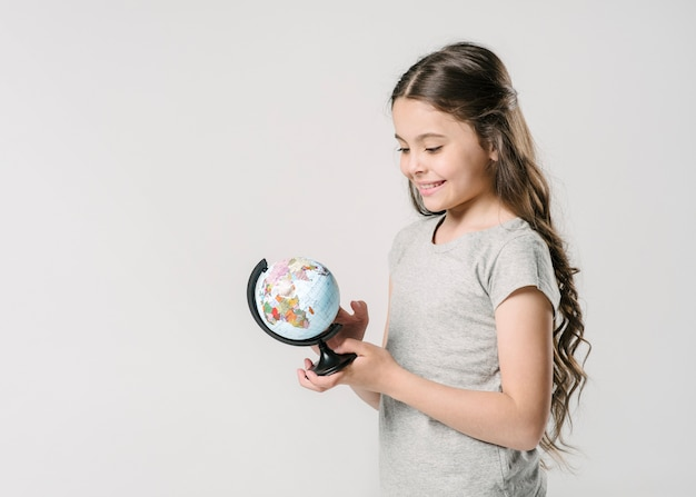 Sweet girl holding globe in studio Free Photo