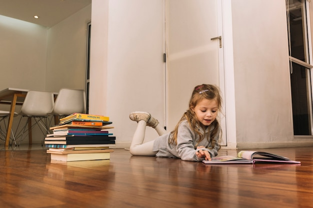 Sweet girl reading books on floor Free Photo