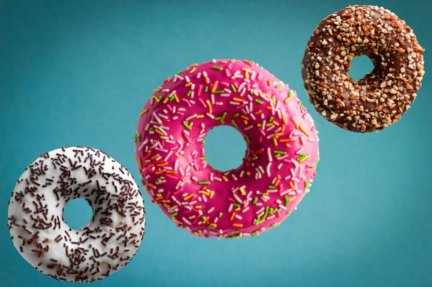 Sweet  glazed donuts flying over blue background, junk food concept Premium Photo