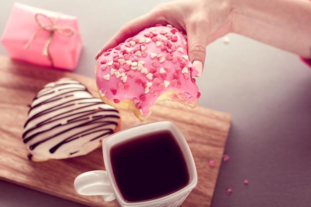 Сладкий пончик в форме сердца в руке с кофе Premium Фотографии