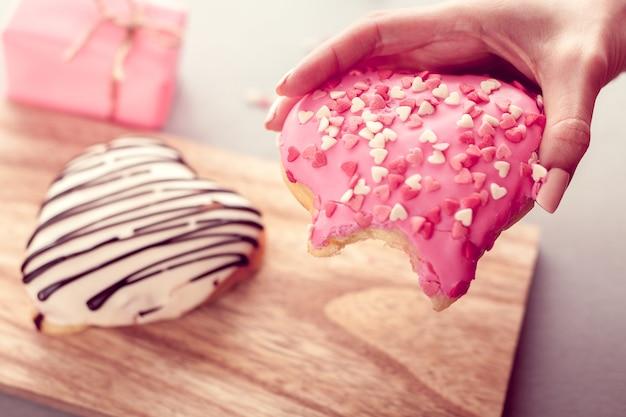 Сладкий пончик в форме сердца в руке Premium Фотографии