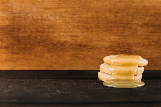 Sweet honey dripping over cookies in front of wooden background Free Photo