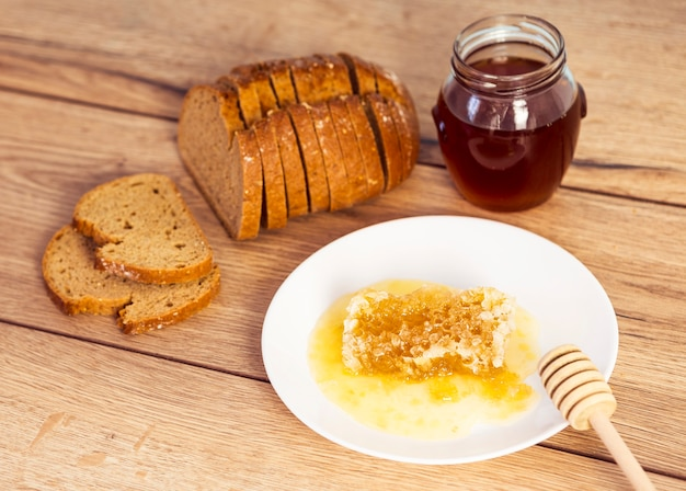 Sweet honeycomb; bread and honey jar over table Free Photo