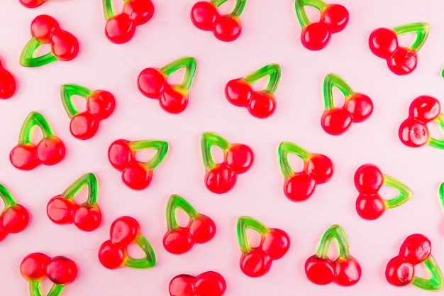Sweet jelly cherry candies on pink surface Free Photo
